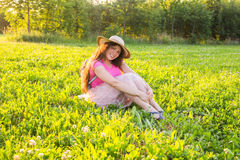 Mooie jonge het lachen ongehoorzame vrouwenzitting op het gras en het glimlachen Royalty-vrije Stock Fotografie