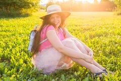 Mooie jonge het lachen ongehoorzame vrouwenzitting op het gras en het glimlachen Royalty-vrije Stock Foto