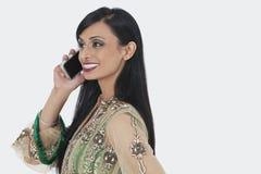 Mooie jonge Indische vrouw in traditioneel slijtage het aanwezig zijn telefoongesprek over grijze achtergrond Royalty-vrije Stock Foto