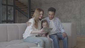 Mooie jonge internationale familie thuis, Afrikaanse Amerikaanse man, Kaukasische vrouw en kleine meisjeszitting op de bank stock videobeelden