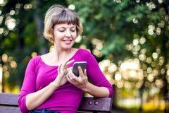 Mooie jonge Kaukasische vrouw die haar smartphone en het glimlachen gebruiken stock foto