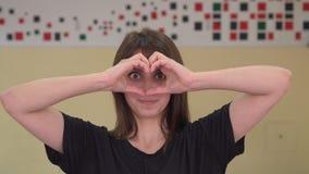 Mooie jonge Kaukasische vrouw die het gebaar van het liefdehart met handen maken stock video