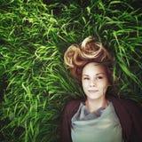 Mooie jonge meditatieve vrouw in het gras. Instagrameffect. Royalty-vrije Stock Foto's