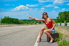 Mooie jonge meisje of vrouw in mini met koffer die langs een weg liften Royalty-vrije Stock Fotografie