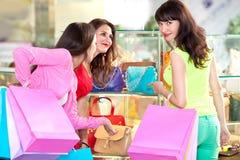 Mooie jonge meisjes met het winkelen zakken in de wandelgalerij stock afbeeldingen