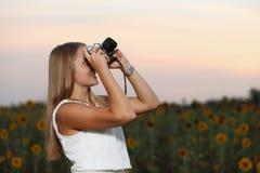 Mooie jonge meisjesfotograaf met fotocamera op aard Stock Foto's
