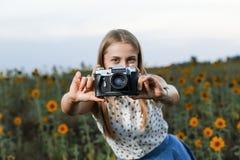 Mooie jonge meisjesfotograaf met fotocamera op aard stock foto