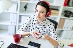 Mooie jonge meisjeszitting in hoofdtelefoons bij bureau in bureau die yoghurt met het rode vullen eten stock fotografie