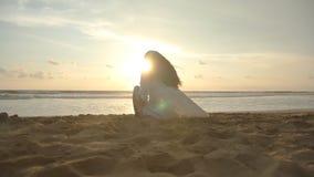 Mooie jonge meisjeszitting op het oceaanstrand in zonsondergangtijd Vrouwenzitting op de gouden zand op zee kust en stock videobeelden