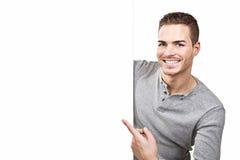 Mooie jonge mens die bij leeg uithangbord tonen Royalty-vrije Stock Foto's