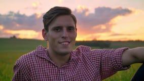 Mooie jonge mens die en camera glimlachen bekijken, zittend op tarwegebied, verbazende aard met zonsondergang op achtergrond stock videobeelden