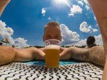Mooie jonge mens die van bier genieten bij de pool stock fotografie
