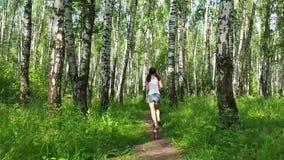 Mooie jonge modelmeisje opleidingslooppas in berk bos, langzame motie stock videobeelden