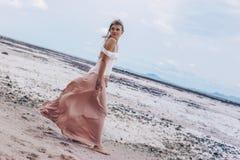 Mooie jonge modieuze vrouw op het strand bij zonsondergang stock foto's