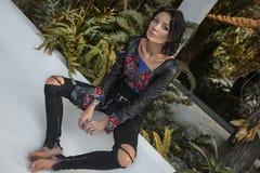 Mooie jonge modieuze vrouw op vloer bij tropische villa stock afbeelding