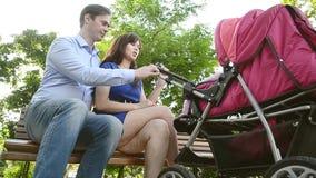 Mooie jonge moeder die met een kinderwagen in park lopen stock footage