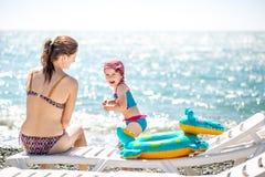 Mooie jonge moeder en dochter die pret hebben die op het overzees rusten Zij zitten op het strand met kiezelstenen op een ligstoe stock foto
