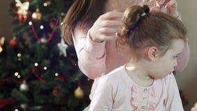 Mooie jonge moeder en dochterzitting op de vloer naast een Kerstboom die, die en een kruik koesteren houden van stock video