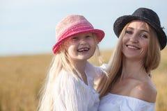 Mooie jonge moeder en haar dochter bij het tarwegebied Stock Foto's