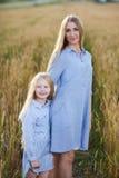 Mooie jonge moeder en haar dochter bij het tarwegebied Royalty-vrije Stock Afbeeldingen