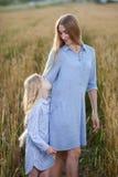 Mooie jonge moeder en haar dochter bij het tarwegebied Stock Fotografie