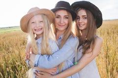 Mooie jonge moeder en haar dochters bij het tarwegebied Stock Fotografie