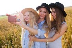 Mooie jonge moeder en haar dochters bij het tarwegebied Royalty-vrije Stock Foto's