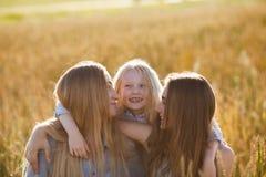 Mooie jonge moeder en haar dochters bij het tarwegebied Royalty-vrije Stock Foto