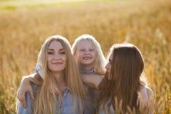 Mooie jonge moeder en haar dochters bij het tarwegebied Stock Afbeelding