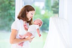 Mooie jonge moeder en haar pasgeboren baby bij een groot venster in a Stock Foto