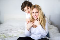 Mooie jonge moeder en zoon die samen op een bed liggen Stock Foto's