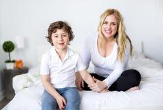 Mooie jonge moeder en zoon die samen op een bed liggen Royalty-vrije Stock Afbeelding