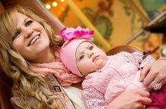 Mooie jonge moeder met baby op vrolijk-gaan-rond royalty-vrije stock afbeeldingen