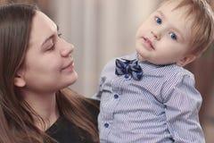 Mooie jonge moeder met een babyjongen in haar wapens thuis Gelukkig familie en moederschapconcept stock foto