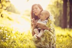 Mooie jonge moeder met haar babyzoon bij aard Portret royalty-vrije stock afbeelding