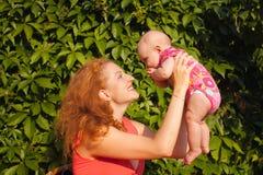 Mooie jonge moeder met horizontale baby Stock Foto's