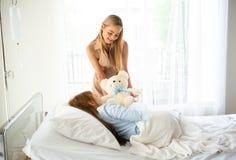 Mooie jonge moeder met teddybeer bezoekende dochter in h stock foto's
