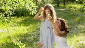 Mooie jonge moeder samen met haar dochter in aard die zeepbels maken stock footage