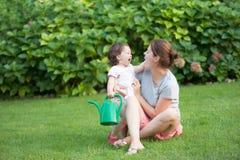 Mooie jonge moederdochter die elkaar glimlachen het groene gras van de de zomerweide stock foto's