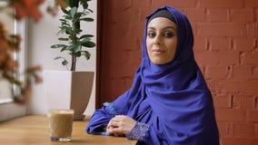 Mooie jonge moslimvrouw in blauwe hijab die en bij camera draaien glimlachen, die in koffie, dame met doordrongen neus zitten stock footage