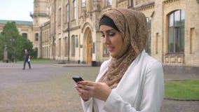 Mooie jonge moslimvrouw in hijab het typen op telefoon en status bij straat dichtbij de bouw, die wit jasje dragen stock video