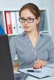 Mooie jonge onderneemster die aan laptop in het bureau werken Royalty-vrije Stock Foto's