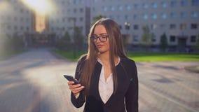 Mooie jonge onderneemster of student die wit overhemd dragen en moderne slimme telefoon in de professionele stad met behulp van, stock video