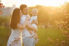 Mooie jonge ouders en hun leuke kleine zoon die en bij de zonsondergang koesteren glimlachen royalty-vrije stock fotografie