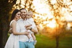 Mooie jonge ouders en hun leuke kleine zoon die en bij de zonsondergang koesteren glimlachen royalty-vrije stock afbeeldingen