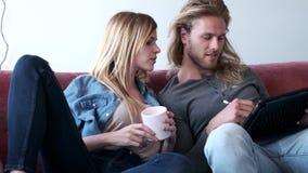 Mooie jonge paartekening met zij digitale tablet terwijl thuis het zitten op bank stock videobeelden