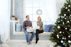 Mooie jonge paarzitting door het venster met Nieuwjaar` s decoratie en Kerstboom Stock Fotografie