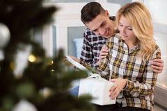 Mooie jonge paarzitting door het venster met Nieuwjaar` s decoratie en Kerstboom Stock Afbeeldingen