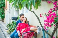 Mooie jonge paarzitting op de bank op mediterrane stadsstraat met bloeiende bomen Liefde, het dateren, Romaans, vreugde en happi Royalty-vrije Stock Foto's