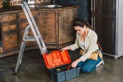 mooie jonge repairwoman met toolbox zitting op vloer royalty-vrije stock foto's